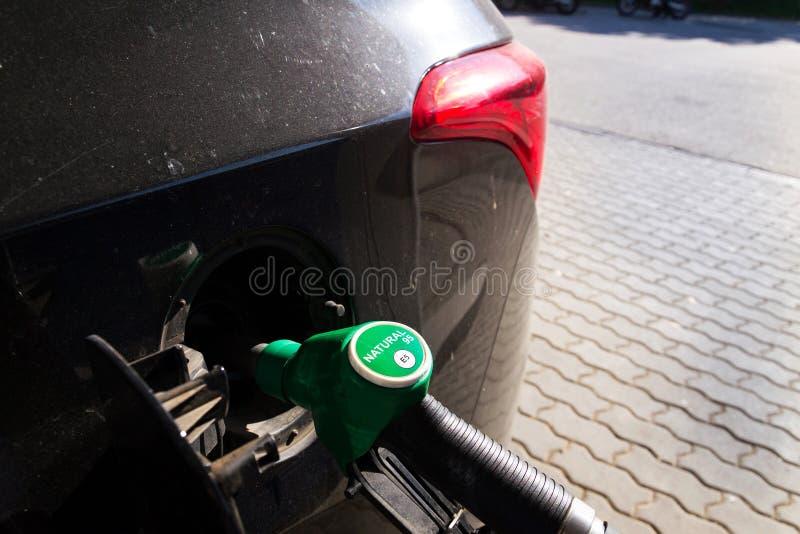 Zapfpistole mit neuer kreisbenzinart füllender Autobehälter EU Kennzeichnungsvon der Tankstellezufuhr, schwarzes Auto stockfotos