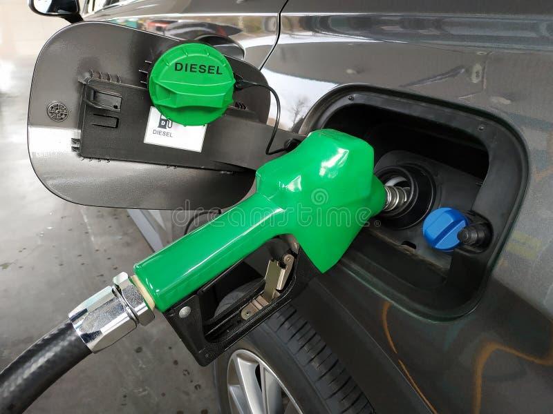 Zapfpistolen, die Dieselkraftstoff im Auto an einer PumpenTankstelle hinzufügen lizenzfreies stockbild
