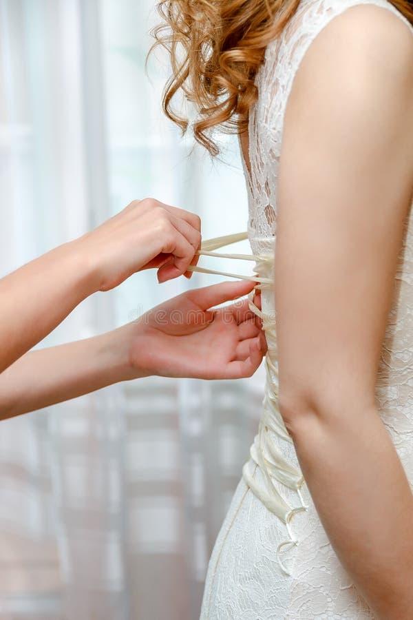Zapinać panny młodej ślubną suknię z bliska zdjęcia stock