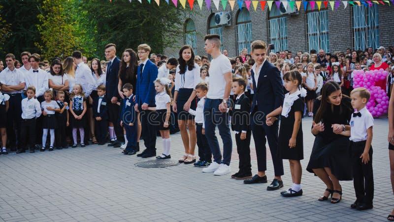 Zaporizhia, Ucrânia - 1º de setembro de 2018: os estudantes da High School guardam primeiro-graduadores pelas mãos e estão em uma fotografia de stock royalty free