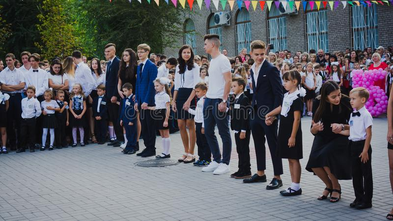 Zaporizhia, Ukraine - September 1, 2018: high school students hold first-graders by the hands and stand on an open-air ruler on royalty free stock photography