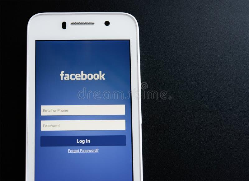ZAPORIZHZHYA,乌克兰- 2014年11月07日:有Facebook社会网络登录画面的白色巧妙的电话在黑表上 免版税库存照片
