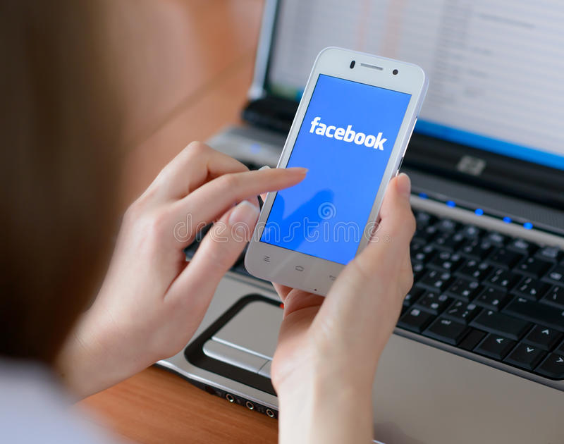 ZAPORIZHZHYA, УКРАИНА - 23-ЬЕ ЯНВАРЯ 2015: Молодая женщина используя применение сети Facebook социальное на ее умном телефоне стоковые изображения rf