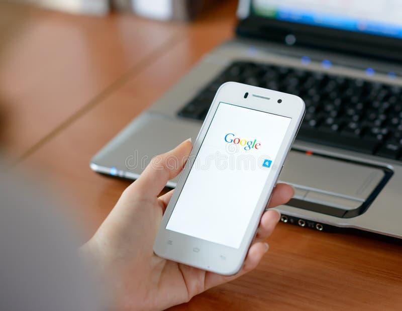 ZAPORIZHZHYA, UCRÂNIA - 23 DE JANEIRO DE 2015: Jovem mulher que usa a busca da Web de Google em seu telefone esperto fotografia de stock