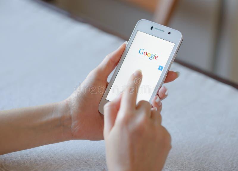 ZAPORIZHZHYA, UKRAINE - 21. NOVEMBER 2014: Junge Frau, die Google-Netz-Suche am intelligenten Telefon verwendet stockbilder