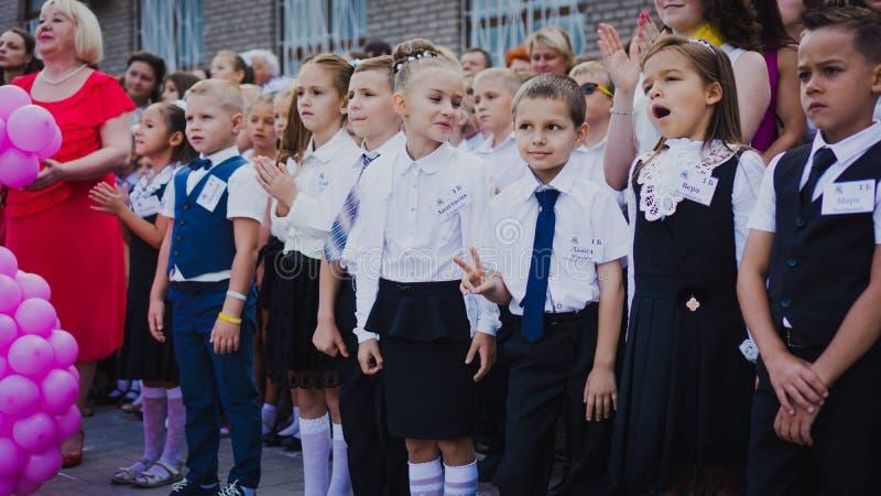 Zaporozhye, Украина - 1-ое сентября 2018: перво-грейдеры стоят на правителе на открытом воздухе с учителями и студентами средней  стоковые изображения