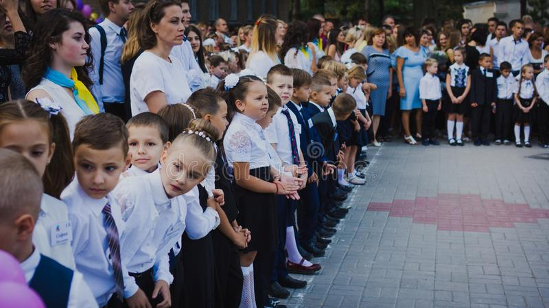 Zaporozhye, Украина - 1-ое сентября 2018: перво-грейдеры стоят на правителе на открытом воздухе с учителями и студентами средней  стоковое изображение rf