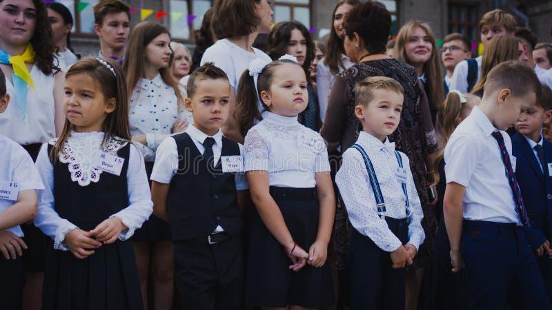 Zaporozhye, Украина - 1-ое сентября 2018: перво-грейдеры стоят на правителе на открытом воздухе с учителями и студентами средней  стоковое фото rf