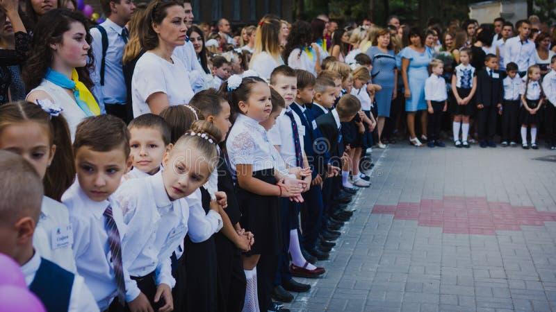 Zaporozhye, Ucrânia - 1º de setembro de 2018: os primeiro-graduadores estão em uma régua no ar livre com professores e estudantes imagem de stock royalty free