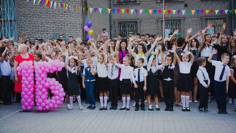 Zaporozhye, Ucrânia - 1º de setembro de 2018: os primeiro-graduadores estão em uma régua no ar livre com professores e estudantes fotos de stock