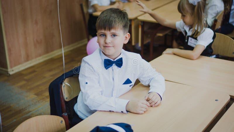 Zaporozhye Ukraina, Wrzesień, - 1, 2018: portret pierwszy równiarka w białej koszula i błękitny łęku krawata obsiadanie przy biur obrazy royalty free