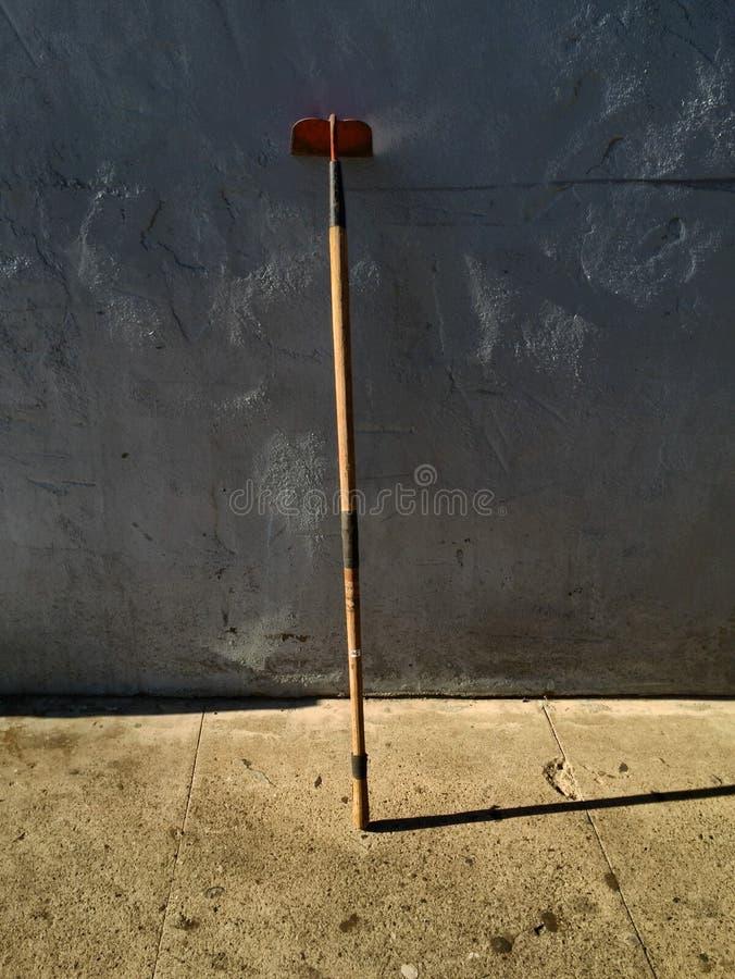 Zappa del giardino che pende contro una parete del cemento immagini stock