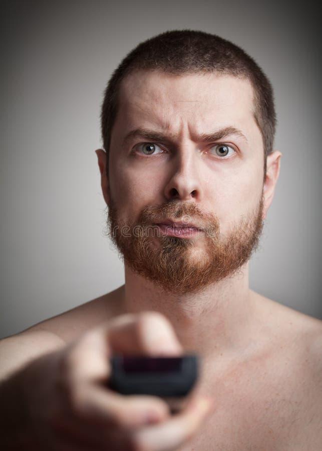 Zapping - gestörter Mann mit Fernsehapparat Fernsteuerungs stockfotos