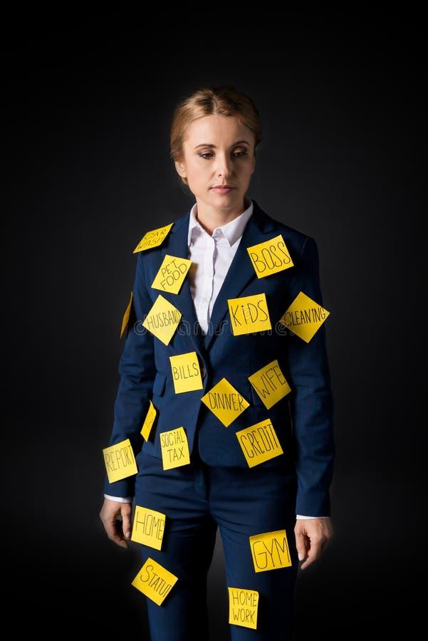 Zapracowana w średnim wieku bizneswoman pozycja z kleistymi notatkami na kostiumu fotografia stock
