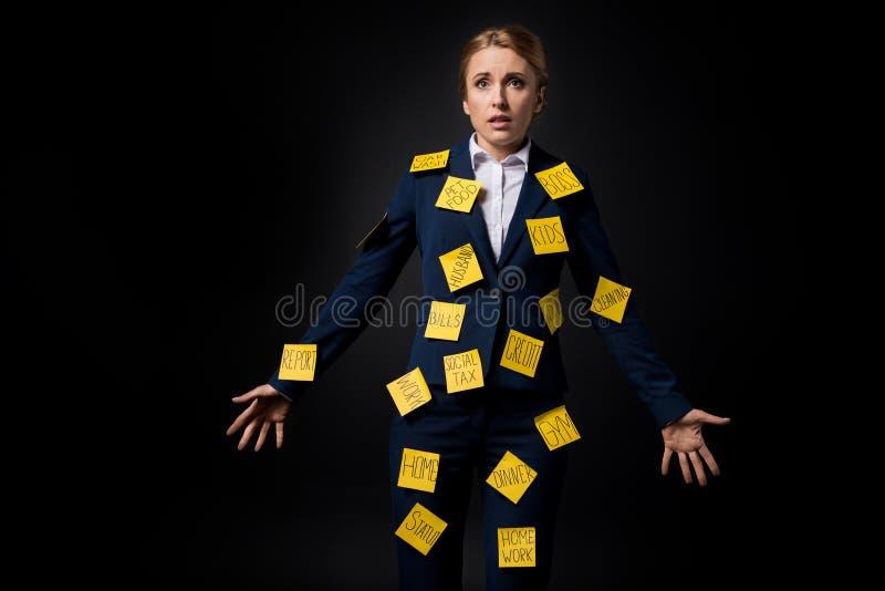 Zapracowana w średnim wieku bizneswoman pozycja z kleistymi notatkami na kostiumu obraz stock