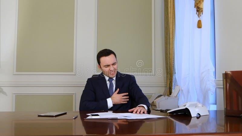 Zapracowany biznesmen uczęszcza rozmowy telefonicza i robi papierkowej robocie i nagle głębokiego ból w jego sercu obraz stock
