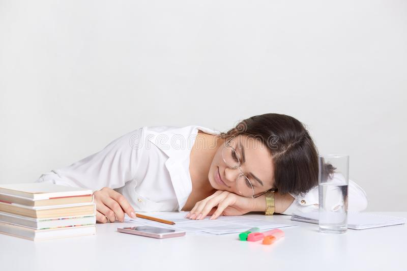 Zapracowany brunetka uczeń opiera przy rękami na biurku, wp8lywy drzema przy miejsce pracy, odczucia zmęczenie, jest ubranym biał fotografia royalty free