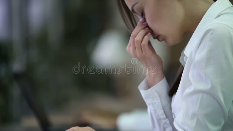 Zapracowany młody biznesowej kobiety nacieranie ono przygląda się, męczył po trudnego dnia przy pracą, fotografia royalty free