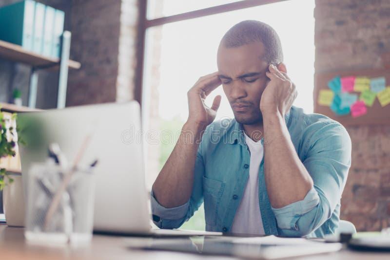 Zapracowany zaakcentowany oliwkowy freelancer ma migrenę i główkowanie dlaczego kończyć projekt Jest w przypadkowy mądrze, przy j fotografia royalty free