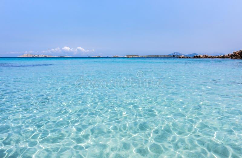 Zapraszający turkusowy morze śródziemnomorskie z odbiciami - pasmo górskie i skały w tle, Capriccioli plaża, Sardinia, I obraz stock