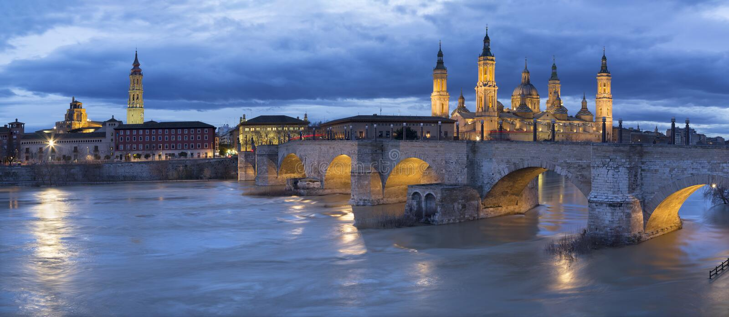 Zaragoza - el paisaje urbano de la torre de Basilica del Pilar de la catedral con el puente de Puente de Piedra fotografía de archivo