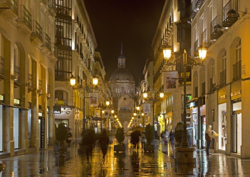 ZARAGOZA, ESPANHA - 1º DE MARÇO DE 2018: A catedral Basílica del Pilar e Calle de Alfonso mim rainly na noite foto de stock