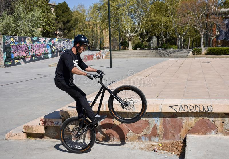 Zaragoza , Spain; 03 23 2019 : sport man wearing helmet, t-shirt, gloves and trousers in black riding a bmx bicycle getting up the stock photo