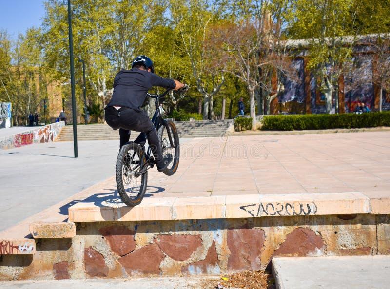 Zaragoza Spanien; 03 23 2019: b?rande hj?lm, t-skjorta, handskar och byxa f?r sportman i svart ridning en bmxcykel som f?r upp royaltyfri foto