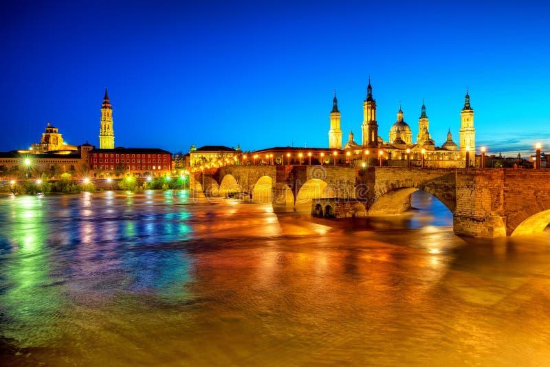 Zaragoza stad, Spanien, sikt över floden till domkyrkan på solnedgången arkivfoto