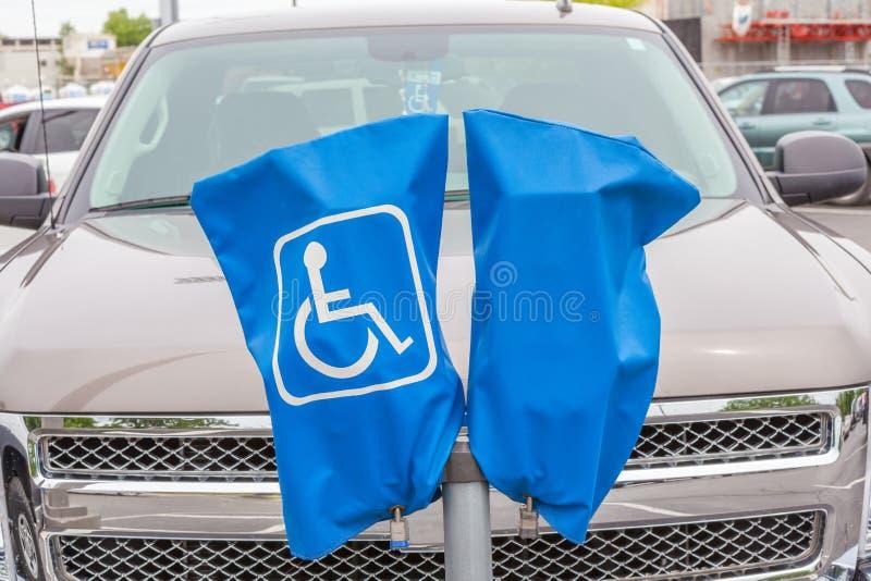 Zarezewowany niepełnosprawny parking znak na błękita stojaku i pokrywie zdjęcia stock
