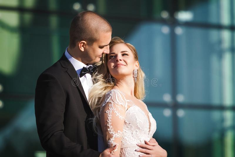 Zarte Braut und das Halten nahe futuristischem Gebäude pflegen lizenzfreie stockbilder