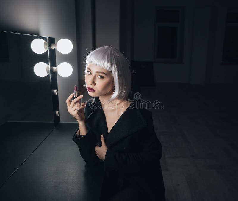 Zarte Frau in der blonden Perücke, die Lippenstift nahe dem Spiegel anwendet lizenzfreies stockbild