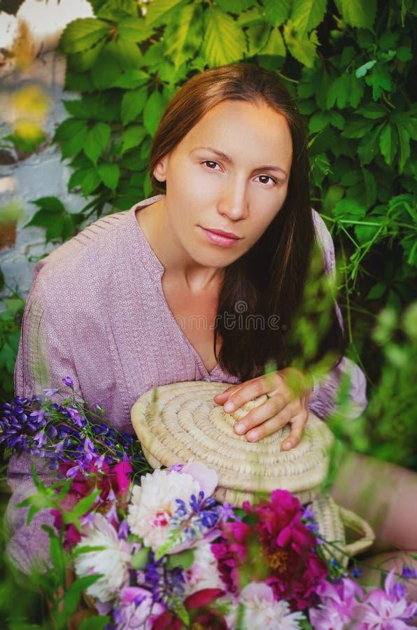 Zarte Frau, die in den grasartigen Dickichten mit einem schönen Blumenstrauß stillsteht lizenzfreie stockfotos