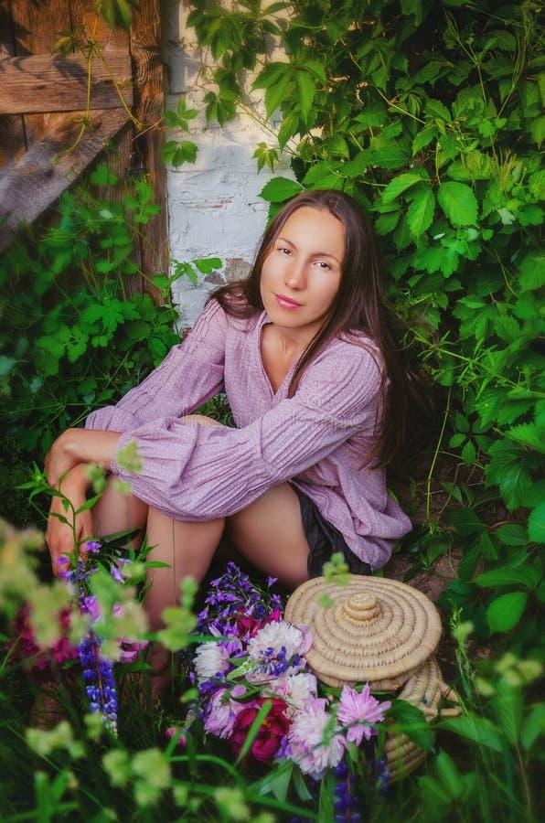 Zarte Frau, die in den grasartigen Dickichten mit einem schönen Blumenstrauß stillsteht stockfotografie