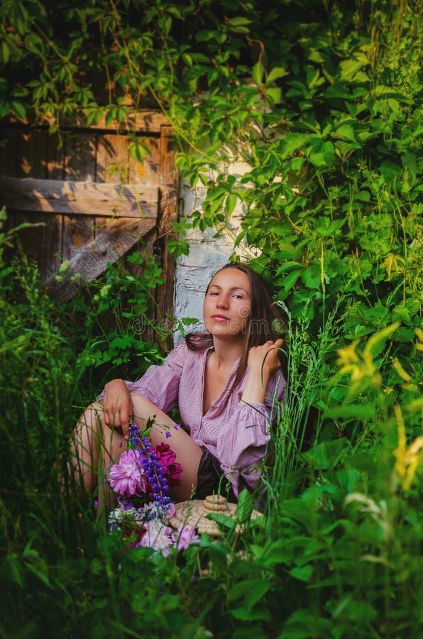 Zarte Frau, die in den grasartigen Dickichten mit einem schönen Blumenstrauß stillsteht lizenzfreies stockfoto