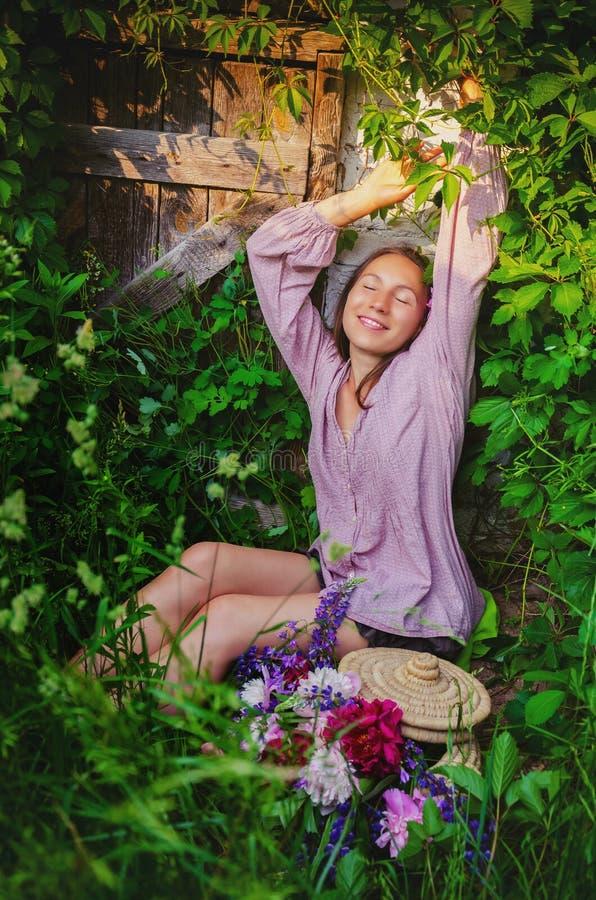 Zarte Frau, die in den grasartigen Dickichten mit einem schönen Blumenstrauß stillsteht lizenzfreies stockbild