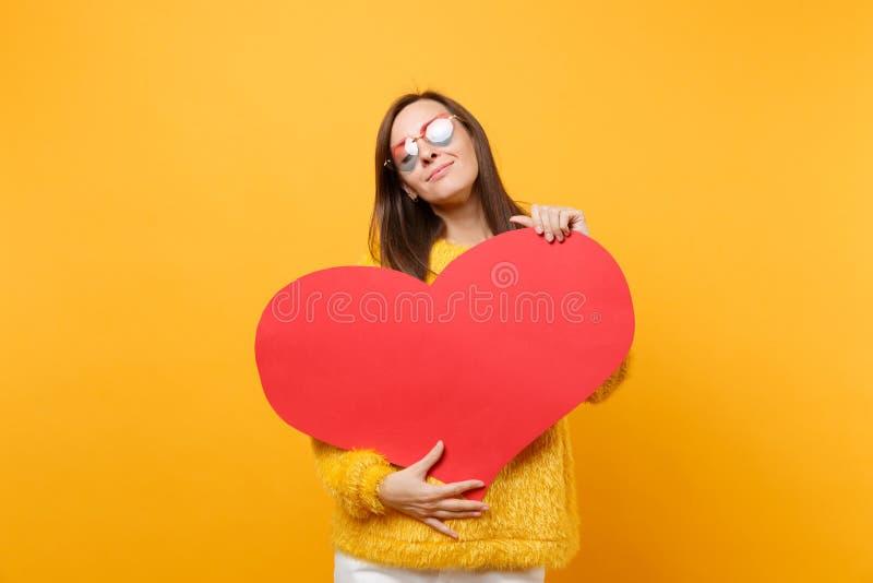 Zarte hübsche junge Frau in der Pelzstrickjacke, Herzgläser Halten, umarmend mit dem leeren leeren roten Herzen lokalisiert auf h lizenzfreies stockbild