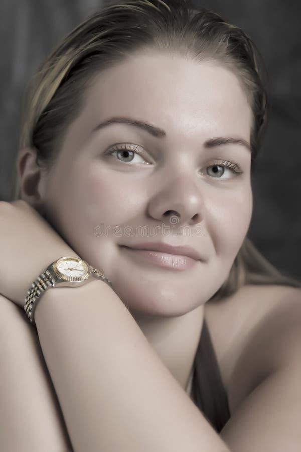 Zarte Lächelnfrau mit Armbanduhr im Tageslicht stockfoto