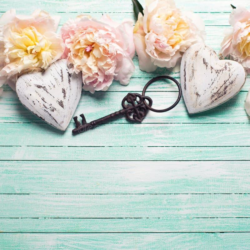 Zarte rosa Pfingstrosenblumen, zwei dekorative Herzen und Weinlese lizenzfreie stockfotos