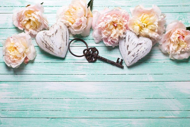 Zarte rosa Pfingstrosenblumen, zwei dekorative Herzen und Weinlese stockbilder