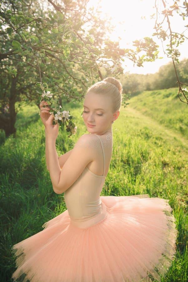 Zarte und romantische Tänzerfrau in den grünen Blumen gestalten an s landschaftlich stockfoto