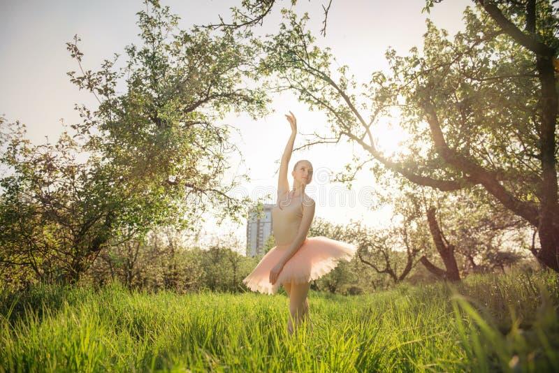 Zarte und romantische Tänzerfrau in der grünen Landschaft bei Sonnenuntergang stockfotos