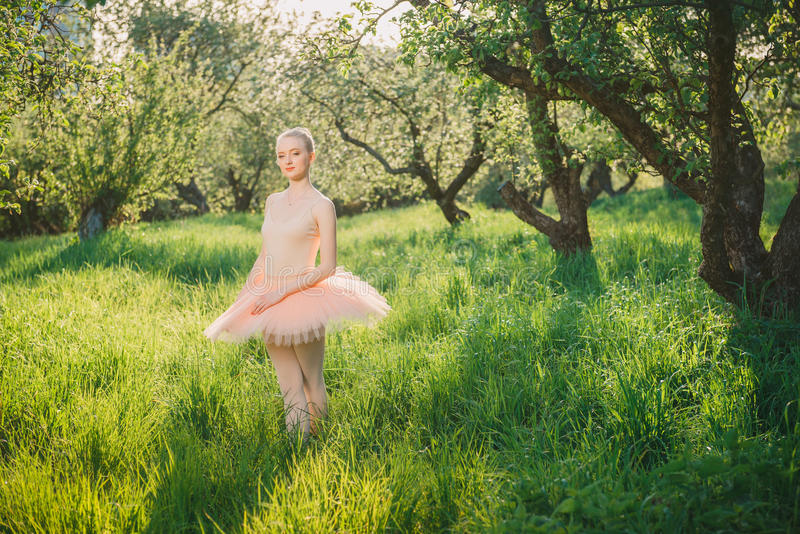 Zarte und romantische Tänzerfrau in der grünen Landschaft bei Sonnenuntergang lizenzfreie stockfotos