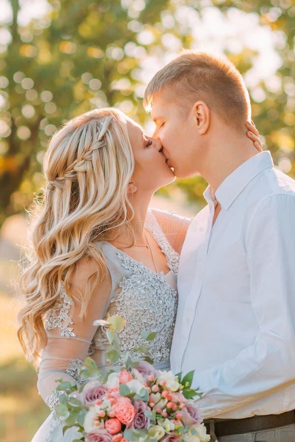 Zarter und sinnlicher Kuss der Braut und des Bräutigams am Hochzeitstag, das Mädchen in einem luxuriösen eleganten Kleid mit tran stockfotos