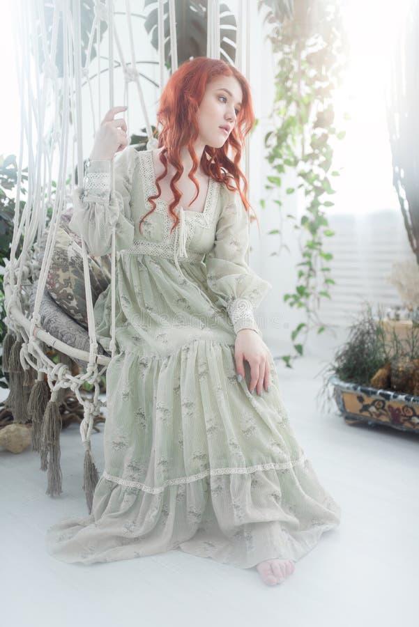 Zartes Porträt einer jungen schönen träumerischen Rothaarigefrau unter Laub im Studio lizenzfreie stockbilder