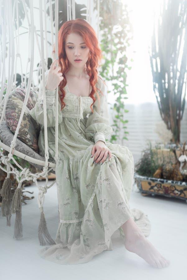 Zartes Porträt einer jungen schönen träumerischen Rothaarigefrau unter Laub im Studio stockfotos