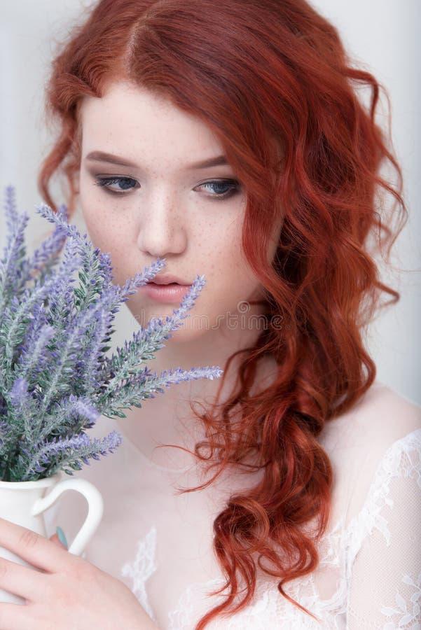 Zartes Retro- Porträt einer jungen schönen träumerischen Rothaarigefrau im schönen weißen Kleid mit Blumenstrauß des Lavendels lizenzfreie stockfotografie