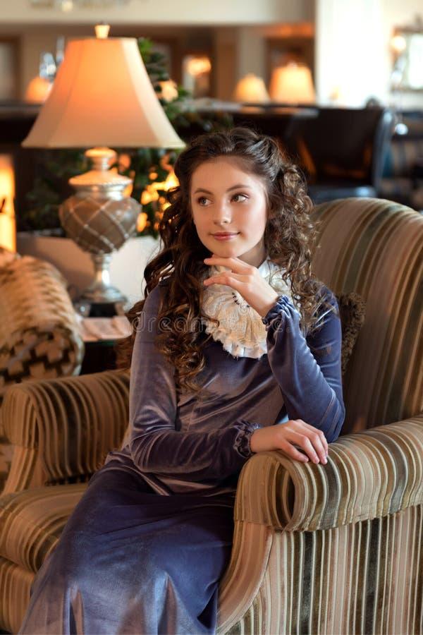 Zartes träumendes Mädchen sitzt in altmodischer Kleidung der Weinlese auf einem Retro- Lehnsessel stockfotografie
