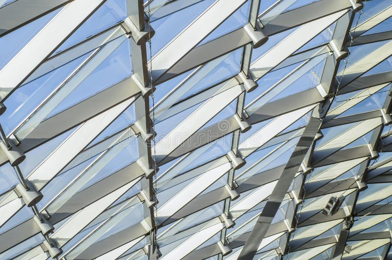 Triangular pattern of transparent glass of a modern roof. Rays of the evening sun. Zaryad park in the center of Moscow. Triangular pattern of transparent glass stock images