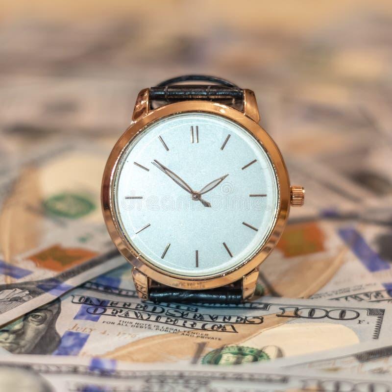 Zarządzanie wydajności pojęcie czas, pieniądze, nadgarstku złocisty zegarek i dolarów amerykańskich banknoty, zdjęcia royalty free